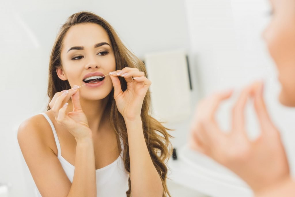 Benefits of Flossing - Woman cleaning teeth with dental floss