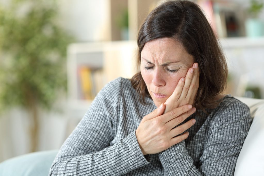 Middle age woman in pain suffering from TMJ touching face sitting on a couch at home